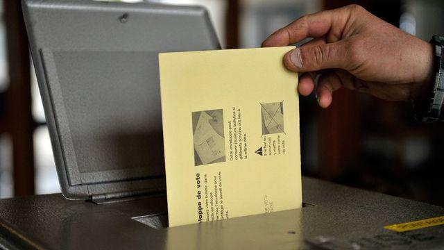 Un citoyen suisse dépose son bulletin de vote dans l'urne. [Dominic Favre - Keystone]