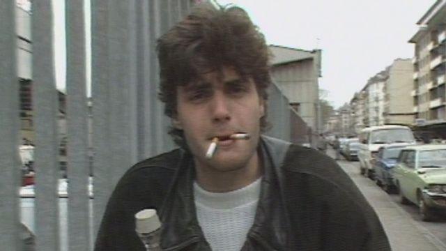 Le présentateur Laurent Deshusses les cigarettes au becs en 1986. [RTS]