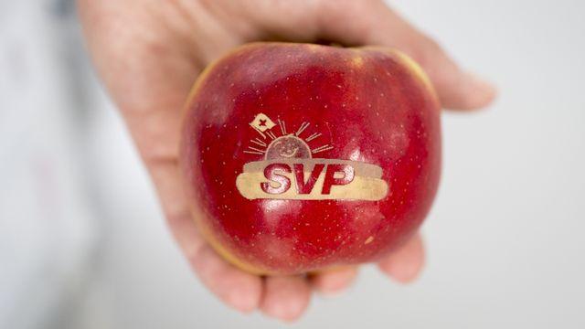 Le logo de l'UDC gravé sur une pomme. [Gian Ehrenzeller - Keystone]
