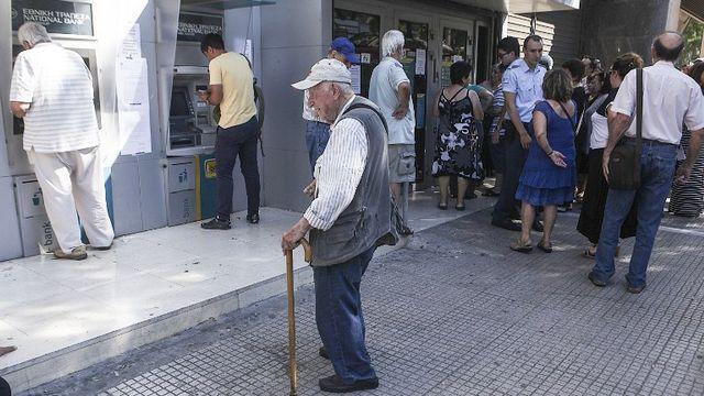 Des citoyens grecs attendent pour retirer de l'argent au bancomat à Athènes, le 9 juillet. [Ayhan Mehmet - Anadolu Agency]