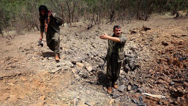 Des membres du PKK inspectent un cratère dans le nord de l'Irak à la suite d'un raid de l'aviation militaire turque, le 29 juillet 2015. [SAFIN HAMED  - AFP]