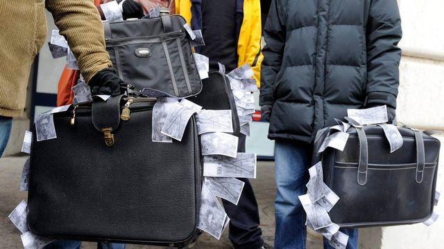 Valises de (faux) billets de banque suisses lors d'une manifestation à Lausanne en 2009. [DOMINIC FAVRE]