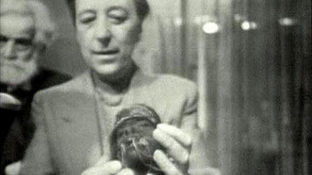 Présentation d'une tête réduite des Jivaro par Marguerite Lobsiger Dellenbach, directrice du Musée d'ethnographie de Genève en 1959. [RTS]