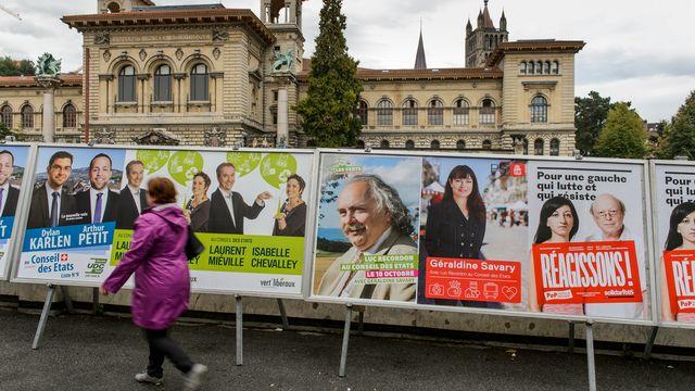 Une dame passe devant les affiches pour les élections fédérales à Lausanne. [Jean-Christophe Bott - Keystone]