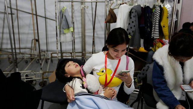 Mère chinoise et son enfant assoupi dans les bras. Les couples sont désormais autorisés à avoir un deuxième enfant. [How Hwee Young - EPA/Keystone]