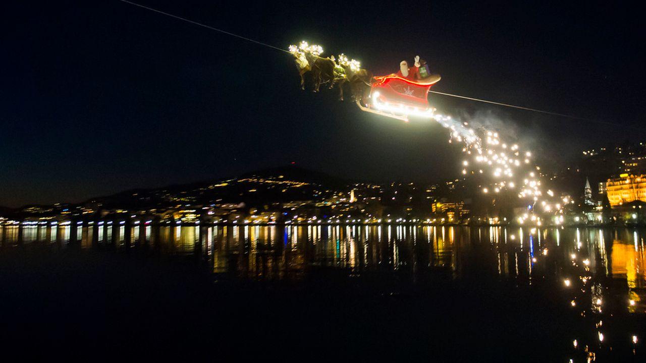 Le Père Noël en plein vol dans son traîneau salue la foule du marché de Noël de Montreux, le 23 décembre 2014.