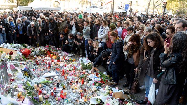 Des dizaines de Parisiens se recueillent devant le Bataclan, théâtre de la plus sanglante des fusillades. [Miguel Medina - AFP]