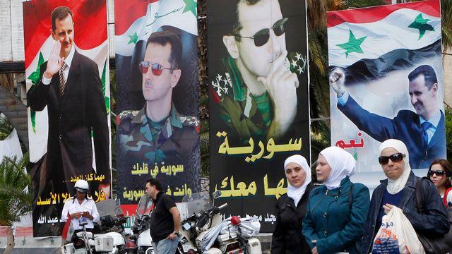 Des posters de soutien à Bachar al-Assad dans les rues de Damas. [Khaled al-Hariri - Keystone]