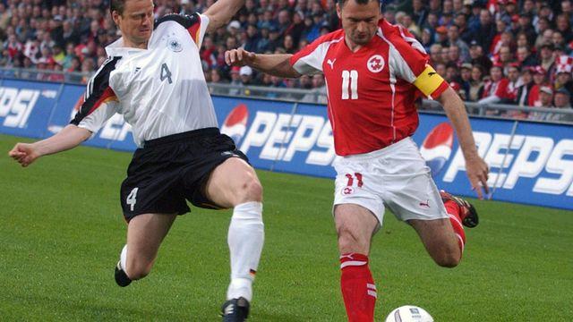 Lors de sa centième sélection en équipe nationale, l'attaquant Stéphane Chapuisat (à droite) tente d'éviter l'intervention du joueur allemand Christian Woerns dans un match amical de préparation pour l'Euro 2004. [Walter Bieri - Keystone]