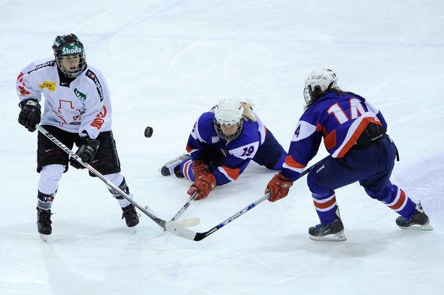 La joueuse suisse Nicole Bullo, à gauche, lutte pour le puck contre les joueuses slovaque lors du match entre la Suisse et la Slovaquie le 13 novembre 2010. [Jean-Christophe Bott - Keystone]