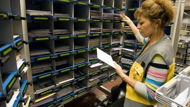 Une employée travaille au casier de tri manuel du courrier dans le Centre logistique de traitement du courrier de Genève.  [Salvatore Di Nolfi - Keystone]
