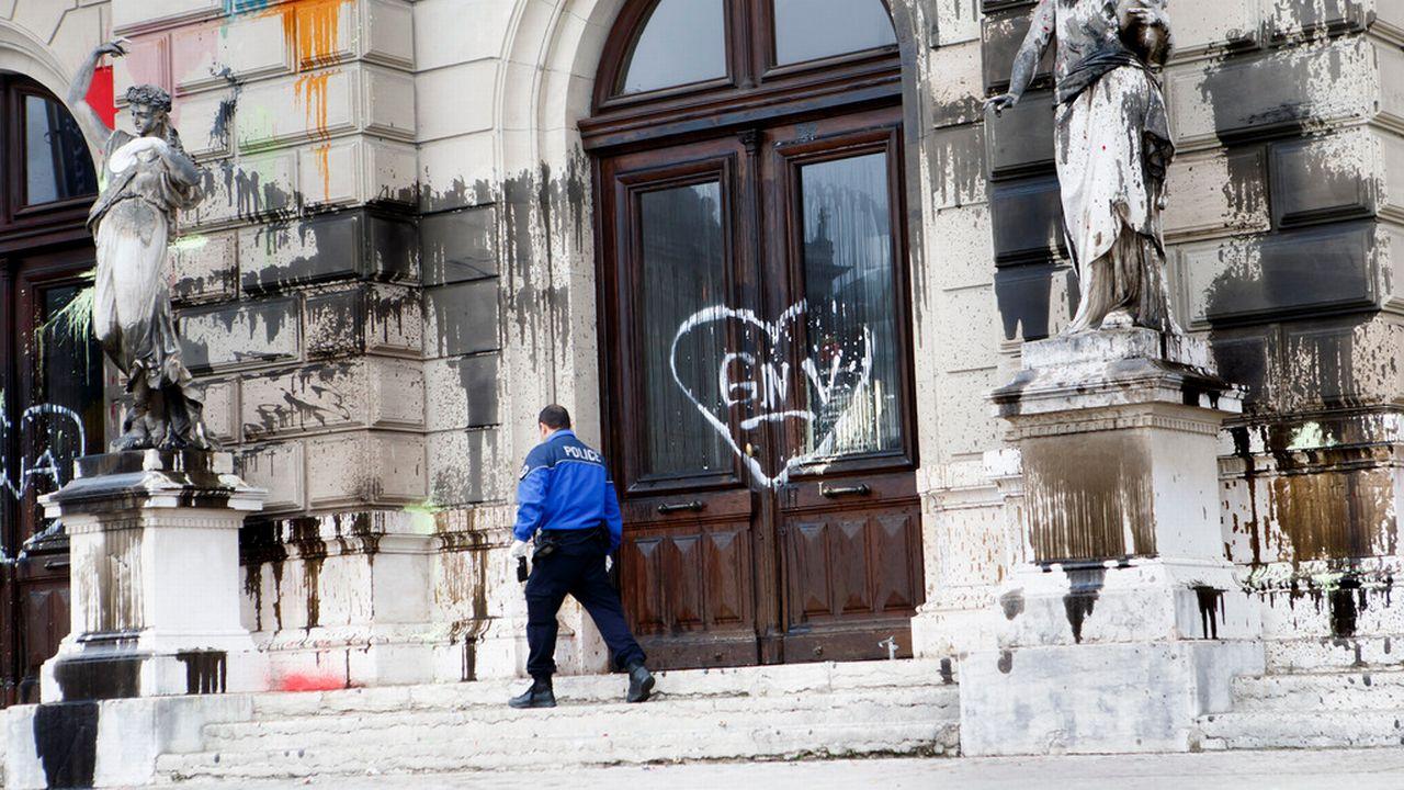 Un policier examine la façade du Grand Théâtre de Genève souillée de tags, 20.12.2015. [Salvatore Di Nolfi - Keystone]
