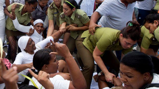 """Des membres des """"Dames en blanc"""" se faisant arrêter à La Havane, dimanche 20 mars. [Keystone]"""