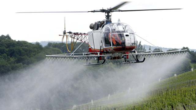 Un hélicoptère effectuant le sulfatage d'un vignoble genevois. [Salvatore Di Nolfi - Keystone]