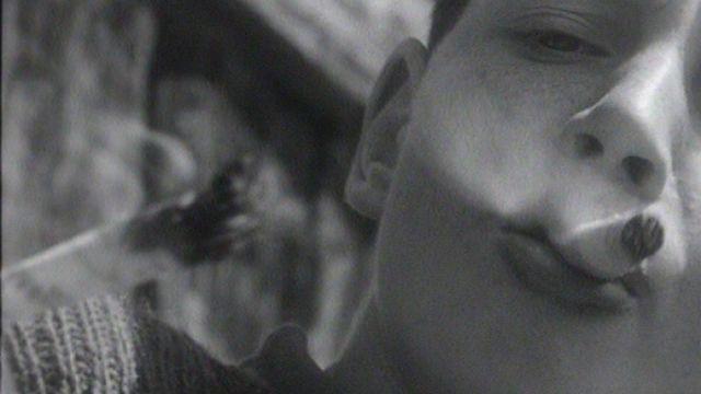 Enfant fumant de l'herbe sèche en 1964. [RTS]