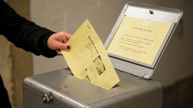 Une personne glisse son bulletin de vote à Yverdon. [Jean-Christophe Bott - Keystone]