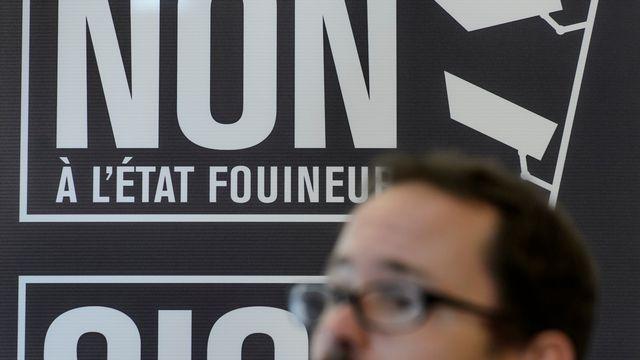 """Une affiche """"Non à l'Etat fouineur"""", derrière Balthasar Glättli (Verts-ZH). [Jean-Christophe Bott - Keystone]"""
