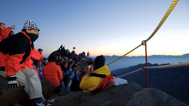 Des touristes admirent le coucher du soleil depuis le Mont Fort (VS). [Keystone]