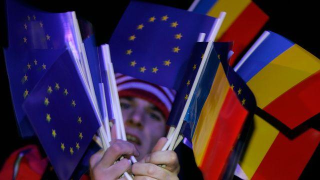 Un homme tient dans ses mains des drapeaux de l'UE et roumains. [Bogdan Cristel - Reuters]