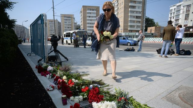 Une femme dépose des fleurs vendredi devant l'ambassade française de Moscou. [Maksim Blinov - Sputnik]