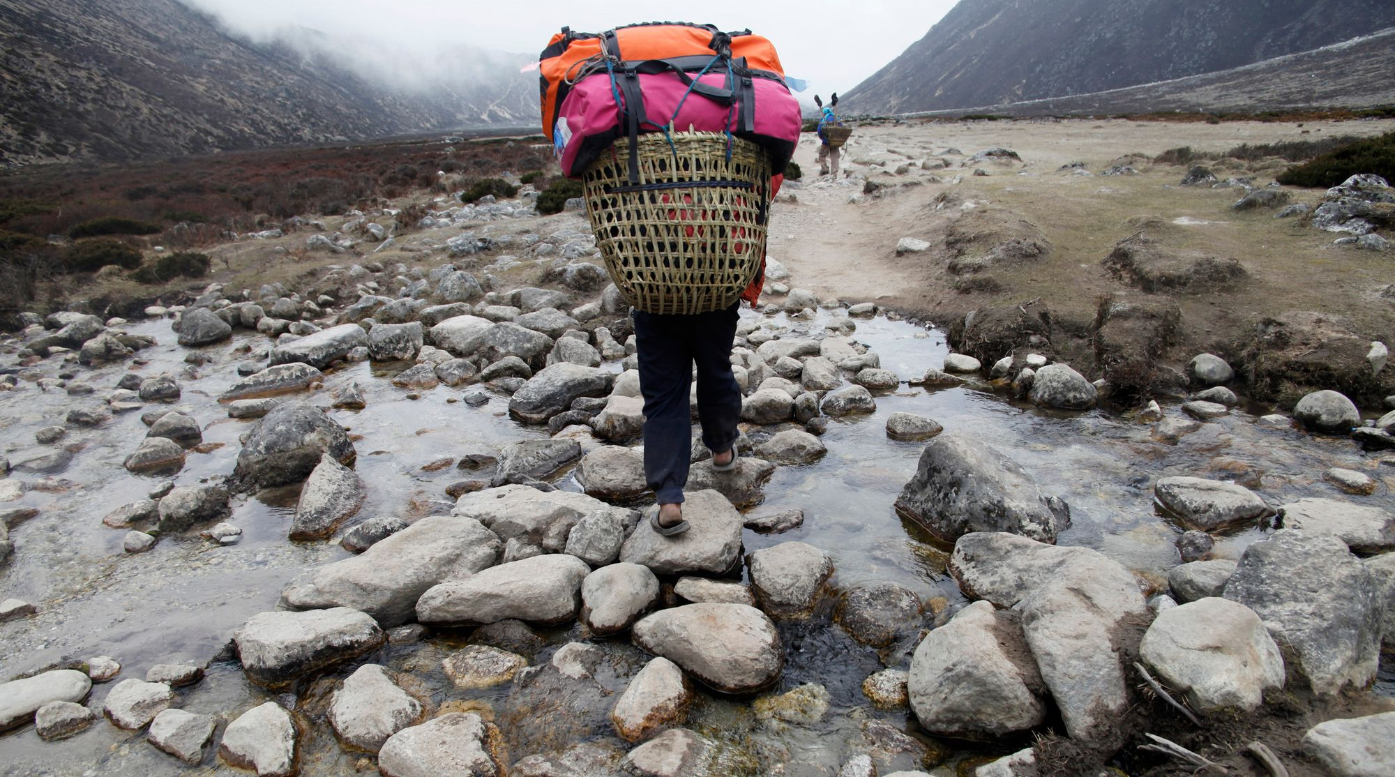 Un porteur transportant les bagages de touristes à travers le village de Periche, sur le Mont Everest.