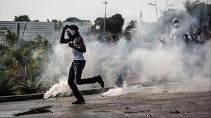 Un manifestant fuit les gaz lacrymogènes à Libreville le 31 août.