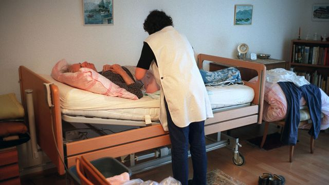 Une infirmière de Spitex donnant des soins à domicile. [Gaetan Bally - Keystone]