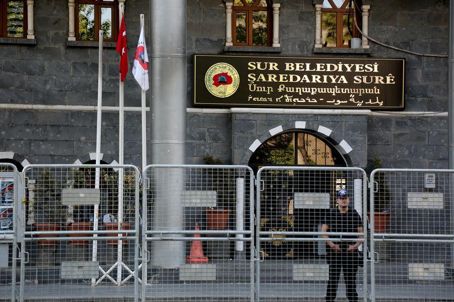 Un policier se tient à devant l'entrée de la mairie de Sur après que la maire a quitté ses fonctions.