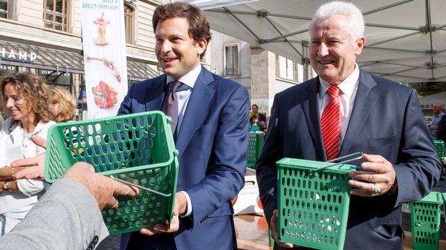 Guillaume Barazzone (à gauche) et Luc Barthassat (à droite) distribuent des poubelles vertes à Genève. [Salvatore Di Nolfi - Keystone]