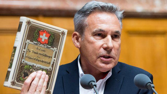 Le conseiller national Adrian Amstutz montre la Constitution fédérale durant le débat. [Peter Schneider - Keystone]