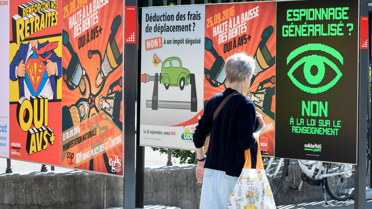Une personne passe devant des affiches sur les différents thèmes des votations fédérales et cantonales à Genève. [Martial Trezzini - Keystone]