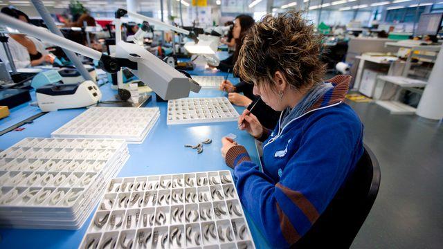Une employée en train de travailler sur des prothèses auditives à Stäfa, dans le canton de Zurich. [Keystone]