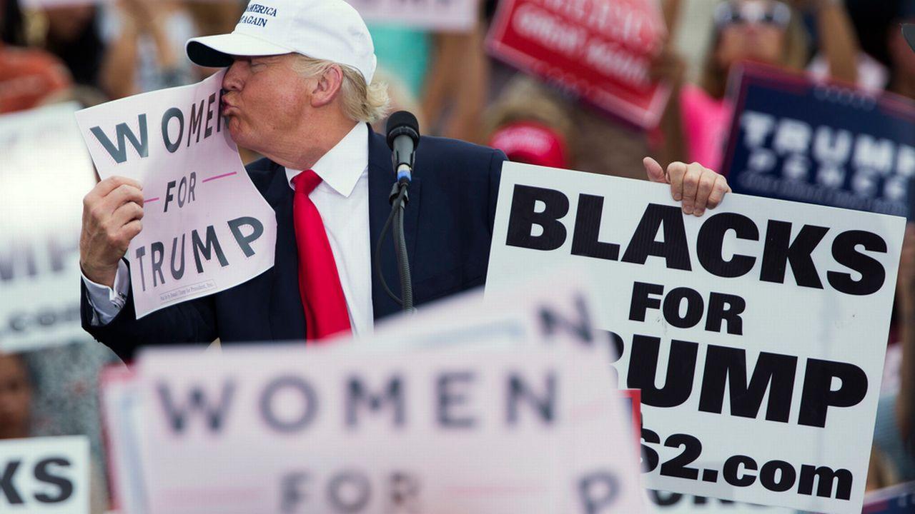 """Donald Trump embrassant un panneau indiquant """"Les femmes pour Trump"""" lors d'un meeting le 12 octobre 2016. [Evan Vucci - Keystone]"""
