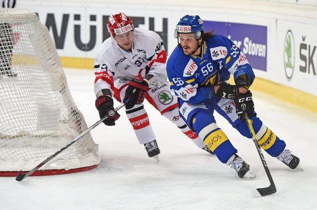 Dino Wieser (en bleu) protège la rondelle devant Alexei Vasilevsky. [Melanie Duchene - Keystone]