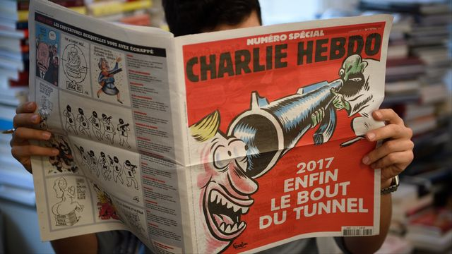 A journalist reads on January 3, 2017 in Paris a special issue of French satirical newspaper Charlie Hebdo to be released in newstands on January 4, almost two years after the January 7, 2015 attack on the offices of the weekly which left 11 dead.  Eric Feferberg / AFP [Eric Feferberg - AFP]