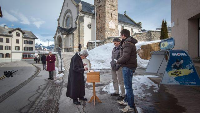 Une habitante du village grison d'Obersaxen Meierhof dépose son bulletin de vote dans l'urne, à côté de l'église du village. [Benjamin Manser - Keystone]