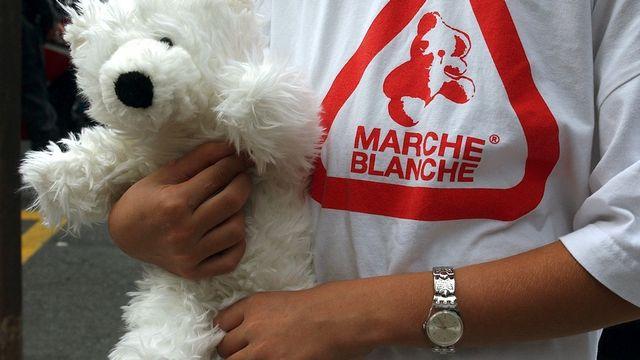 Une jeune fille portant un T-shirt avec le logo de la marche blanche. [Martial Trezzini - Keystone]