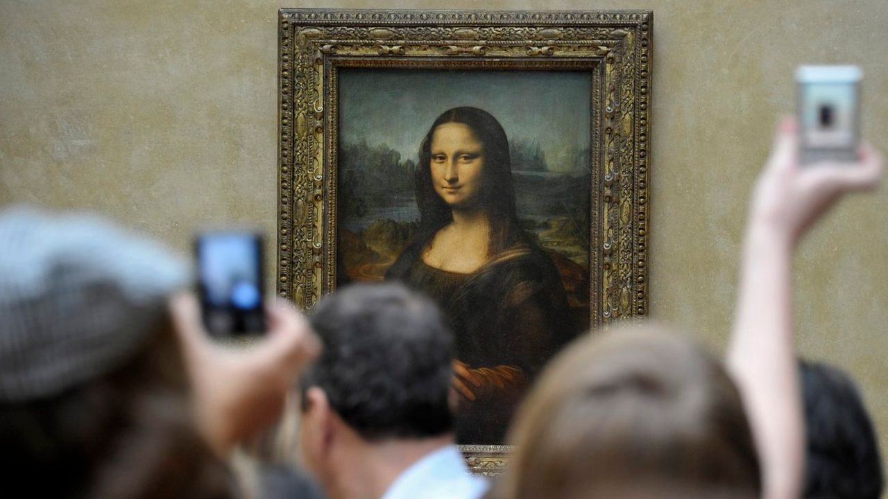 Des visiteurs du Louvre à Paris devant la Joconde de Léonard de Vinci. [HORACIO VILLALOBO - KEYSTONE]