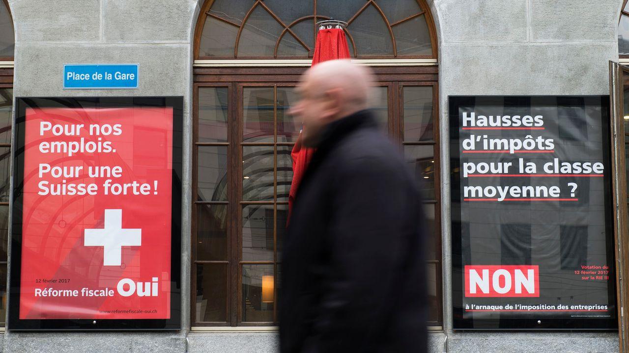 Deux affiches placardées à Fribourg concernant la votation du 12 février sur la RIE III. [Thomas Delley - Keystone]