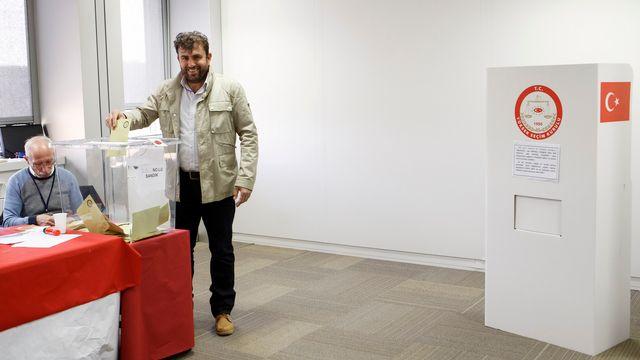 Un homme dépose son bulletin de vote concernant le référendum qui doit donner plus de pouvoir au président Erdogan au consulat de Turquie à Genève le 28 mars 2017. [Salvatore Di Nolfi - Keystone]