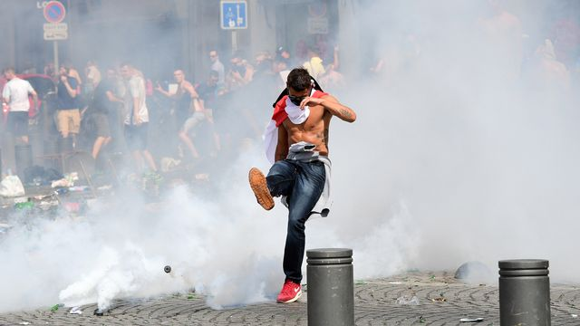 Un hooligan anglais à Marseilles lors de l'Euro 2016 de foot en France. An England fan kicks away a tear gas canister after tear gas was released by French police in the city of Marseille, southern France, on June 11, 2016, ahead of the Euro 2016 football match between England and Russia.  Léon Neal AFP [Léon Neal - AFP]