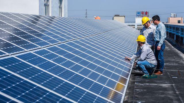 Des techniciens inspectent des panneaux solaires sur un toit de Cixi City, dans l'est de la Chine. [Xinhua/Xu Yu - AFP]