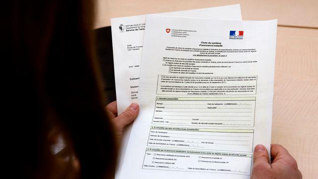 Une journaliste lit le formulaire sur le choix du système d'assurance maladie pour les frontaliers. [Salvatore Di Nolfi - Keystone]