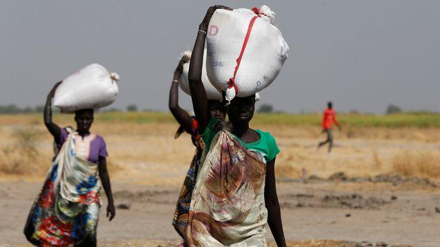 Des femmes du village de Nimini, au Soudan du Sud, transportant des sacs de vivres. [Siegfried Modola - Reuters]