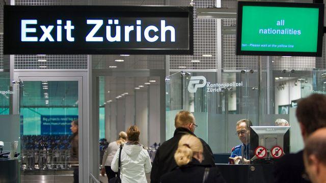 Des voyageurs au contrôle des passeports à l'aéroport de Zurich. [Gaëtan Bally - Keystone]