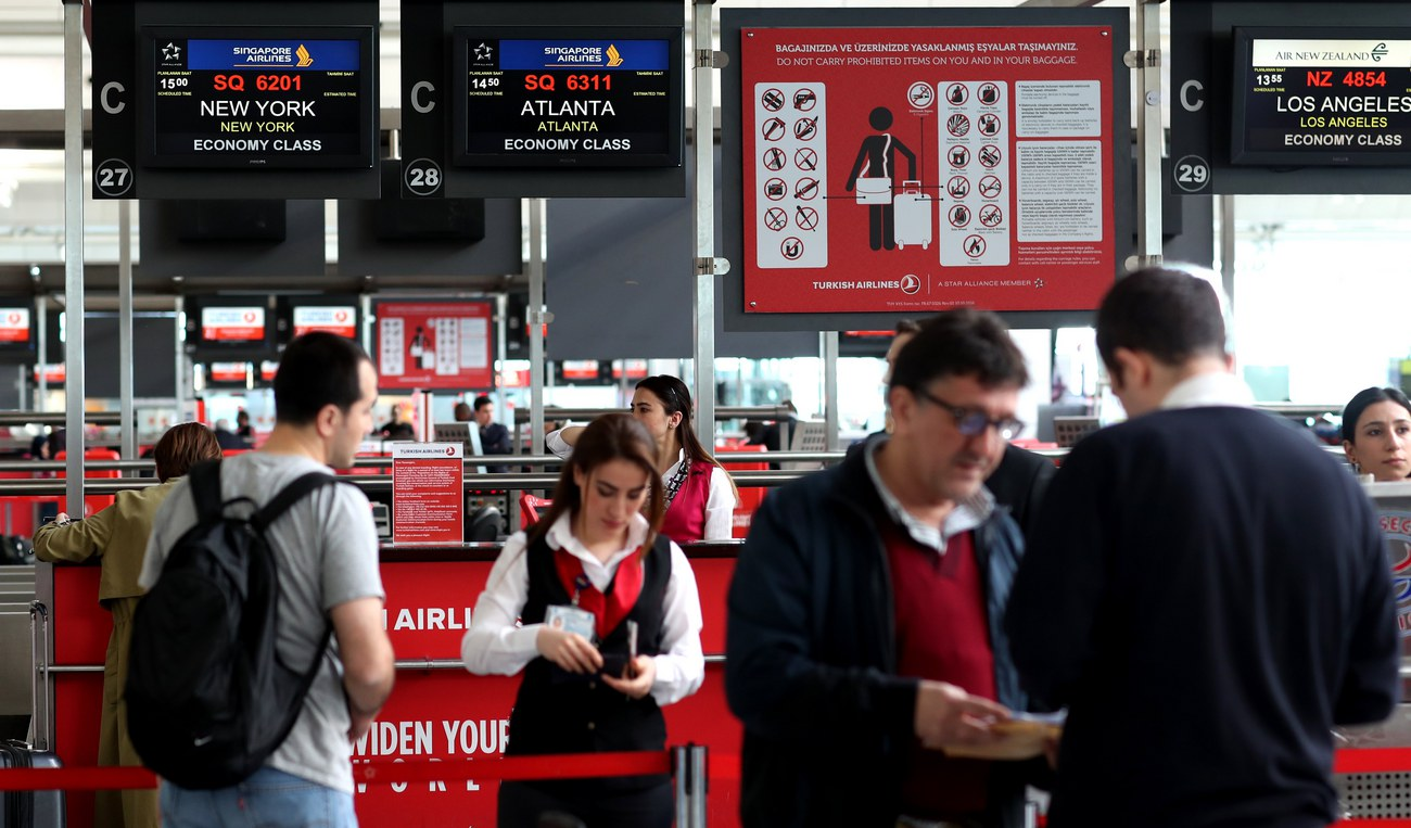 Des passagers de Turkish Airlines devant un desk à l'aéroport d'Istanbul.