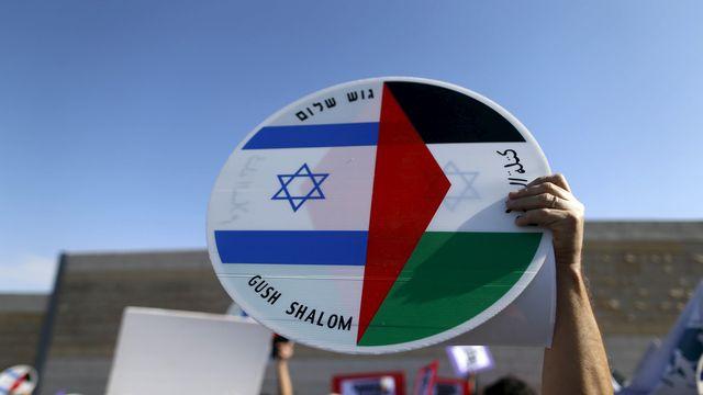 Un manifestant tient un panneau avec le drapeau de la Palestine et celui d'Israël. [Ammar Awad - Reuters]