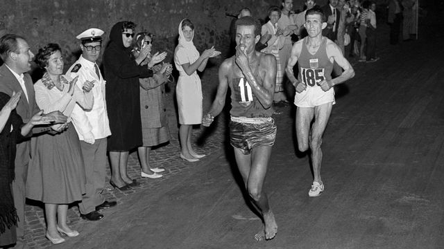 Rome 1960: l'Ethiopien Abebe Bikila court, nus pieds, vers la victoire dans le marathon.  Ethiopian athlete Abebe Bikila runs barefoot for victory in the Rome 1960 Olympic Games marathon, after passing Moroccan Abdeslam Radi, on September 10.  EPU / AFP [10 septembre 1960: l'Ethiopien Abebe Bikila court, nus pieds, vers la victoire à Rome. - EPU/AFP]