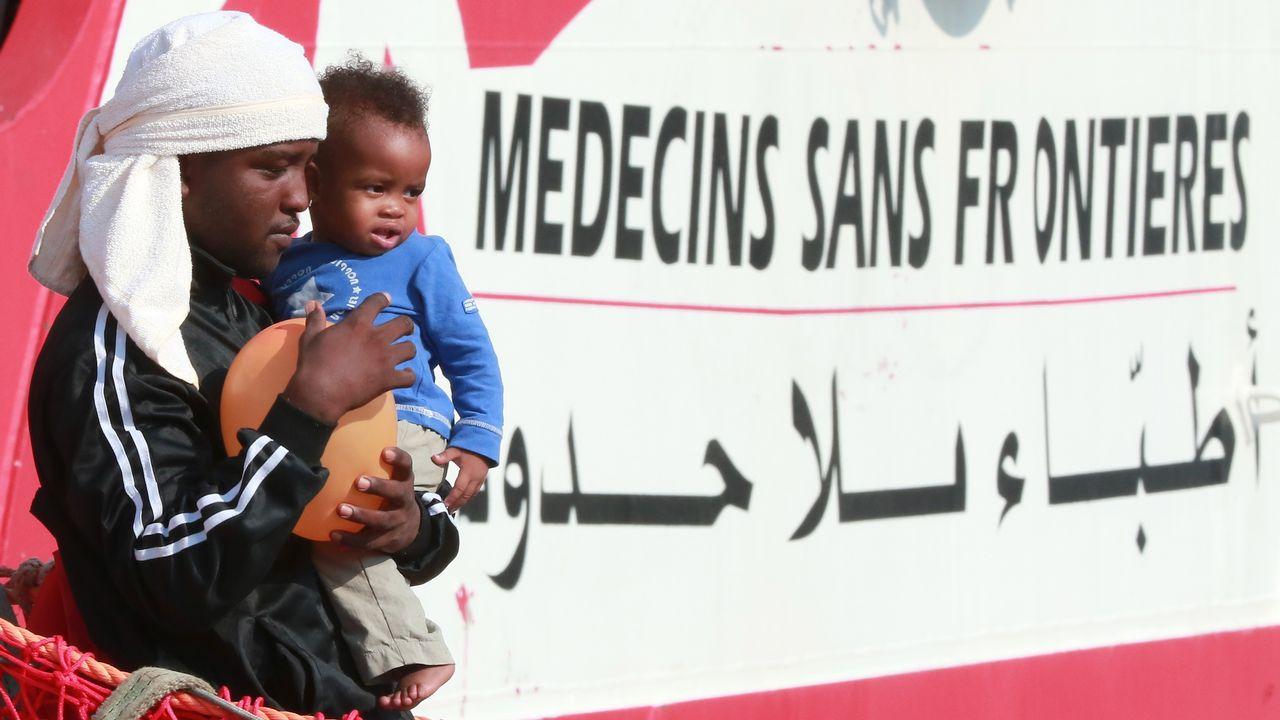Un migrant et un enfant descendent du bateau Vox Prudence de l'ONG Médecins sans frontières le 14 juillet 2017. [CARLO HERMANN - AFP]