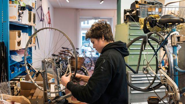 Un apprenti en mécanique vélo dans son atelier à Zurich. [Christian Beutler - Keystone]